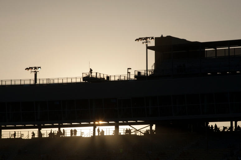 Fans in the grandstands are silhouetted by the setting sun on Friday, March 1, 2013 at Phoenix International Raceway. Aaron Lavinsky/The Arizona Republic