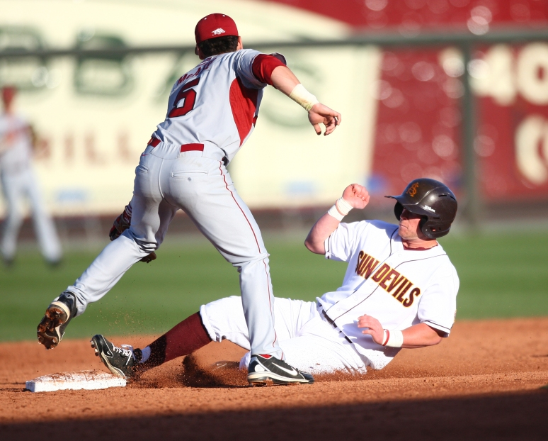 ASU infielder Jake Peevyhouse slides into second as Arkansas shortstop Brett McAfee attempts to tag him out during the Coca-Cola Classic on Thursday, Feb. 28, 2013 at Surprise Stadium. Aaron Lavinsky/The Arizona Republic