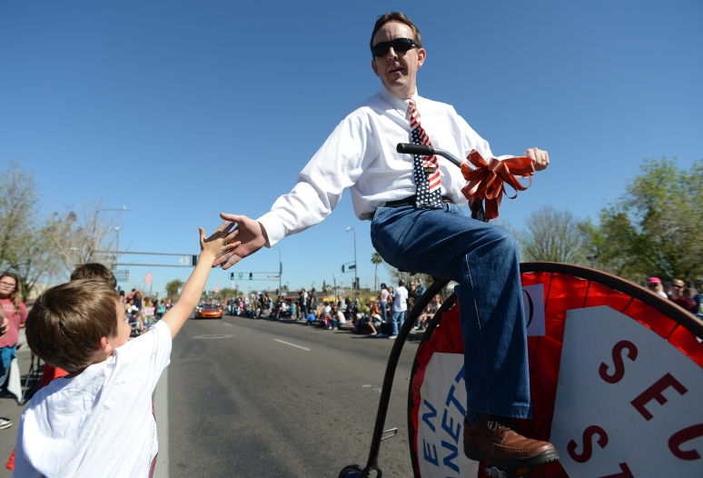 Arizona Secretary of State Ken Bennett high fives parade goers while riding a vintage bicycle during the Chandler Ostrich Festival Parade on March 2, 2013. Aaron Lavinsky/The Arizona Republic