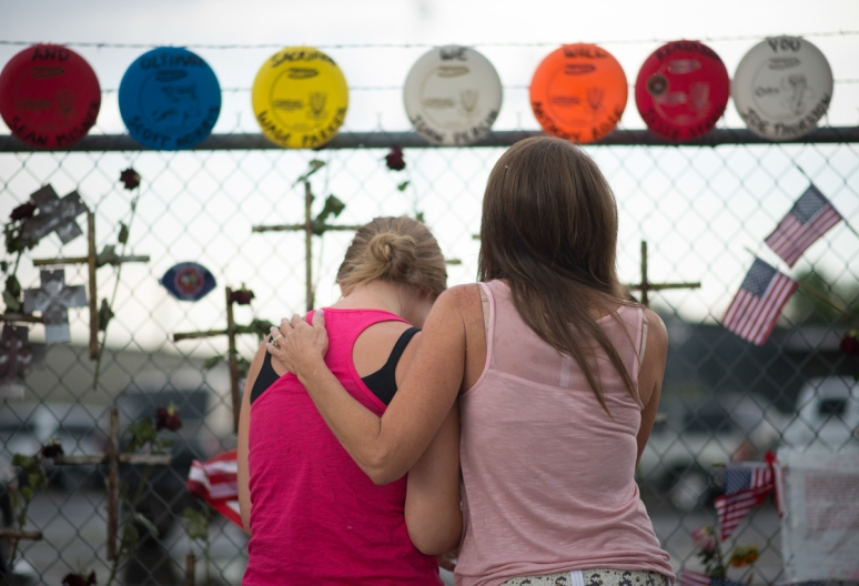 Carrie Parker-Morena (left) is consoled by her aunt, Janae Parker Haremza. Wade Parker, the brother of Parker-Morena and the nephew of Haremza, was among the 19 firefighters killed June 30 in the Yarnell Hill Fire. (Aaron Lavinsky/The Arizona Republic)