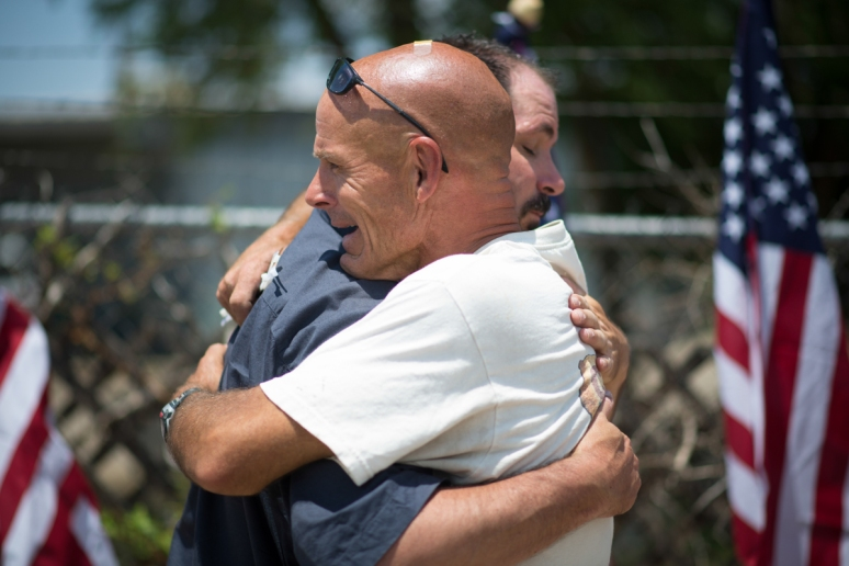 Chris Lyons shares an emotional moment with Steve Fine after setting up 19 American flags at a memorial at the Granite Mountain Hot Shot's fire station in Prescott on Wednesday, July 3, 2013.  (Aaron Lavinsky/The Arizona Republic)