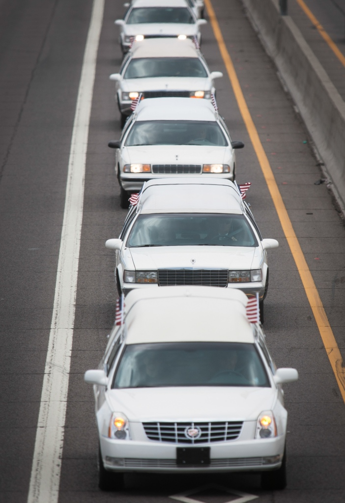 The bodies of the 19 members of the Granite Mountain hotshot crew killed in the Yarnell Hill Fire are escorted from downtown Phoenix back to Prescott along Interstate 17 North on Sunday, July 7, 2013 in Phoenix. (Aaron Lavinsky/The Arizona Republic)