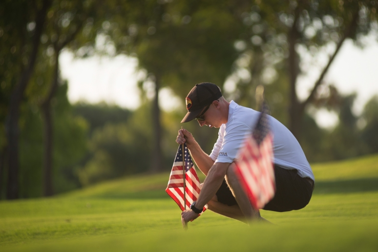 Brendan McDonough, the surviving 20th member of the Granite Mountain Hotshots, makes sure that an American flag stands upright on a practice green at Gainey Ranch Golf Club in Scottsdale on Aug. 2, 2013 (Aaron Lavinsky/The Arizona Republic)